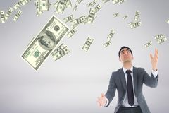 Bedrijfsmens die geldregen tegen witte achtergrond bekijken Stock Foto's