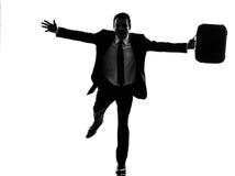 Bedrijfsmens die gelukkig wapens uitgestrekt silhouet in werking stellen stock foto