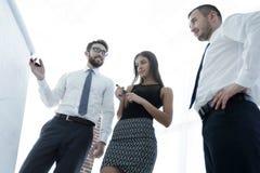 Bedrijfsmens die iets op een whiteboard tonen aan zijn collega's Royalty-vrije Stock Foto's