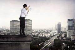 Bedrijfsmens die megafoon met behulp van die aan de stad spreken Stock Foto's