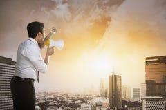 Bedrijfsmens die megafoon met behulp van die aan de stad spreken Stock Afbeeldingen