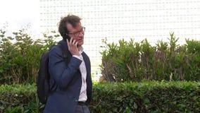Bedrijfsmens die met rugzak in park in stad lopen die op de gelukkige telefoon spreken stock video