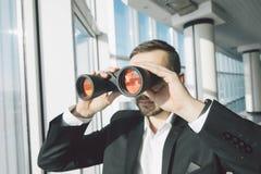 Bedrijfsmens die met verrekijkers kijken Stock Afbeelding
