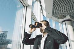 Bedrijfsmens die met verrekijkers kijken Stock Foto's