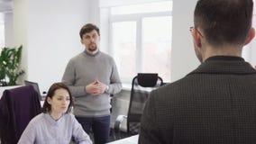Bedrijfsmens die met zijn collega's in bureau spreken stock videobeelden
