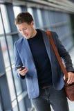 Bedrijfsmens die mobiele telefoon app in luchthaven met behulp van royalty-vrije stock fotografie