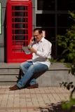 Bedrijfsmens die mobiele telefoon rode klassieke Engelse telefoon BO met behulp van Royalty-vrije Stock Afbeelding