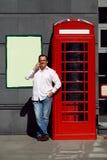 Bedrijfsmens die mobiele telefoon rode klassieke Engelse telefoon BO met behulp van Stock Afbeelding