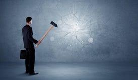 Bedrijfsmens die muur met een hamer raken Stock Fotografie