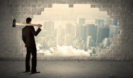 Bedrijfsmens die muur met hamer op stadsmening raken Royalty-vrije Stock Fotografie