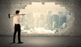 Bedrijfsmens die muur met hamer op stadsmening raken stock foto's