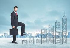 Bedrijfsmens die omhoog op hand getrokken gebouwen in stad beklimmen Stock Foto