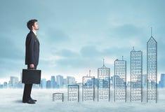 Bedrijfsmens die omhoog op hand getrokken gebouwen in stad beklimmen stock foto's