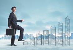 Bedrijfsmens die omhoog op hand getrokken gebouwen in stad beklimmen royalty-vrije stock fotografie