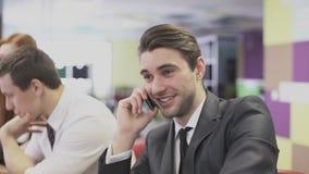 Bedrijfsmens die op de telefoon op het kantoor spreken stock videobeelden