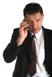 Bedrijfsmens die op de telefoon spreken die sommige ernstige overeenkomsten bespreken Stock Foto's