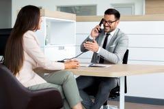 Bedrijfsmens die op de telefoon spreken terwijl in een vergadering stock afbeeldingen