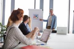 Bedrijfsmens die op grafieken op flipchart tijdens de vergadering richten Stock Foto