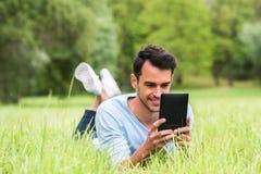 Bedrijfsmens die op het groene gras met zijn apparaat liggen stock foto