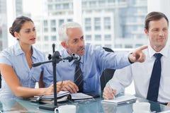 Bedrijfsmens die op iets in een conferentie richten Stock Foto's