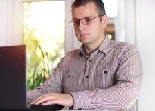 Bedrijfsmens die op kantoor met laptop werken stock afbeelding