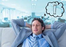 Bedrijfsmens die op laag van cocktail tegen onscherp blauw bureau dromen Stock Foto's