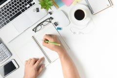 Bedrijfsmens die op leeg notitieboekje op bureau schrijven stock afbeeldingen