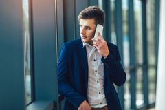 Bedrijfsmens die op smartphone spreken die camera bekijken stock afbeeldingen