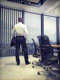 Bedrijfsmens die op stad door een bureauvenster kijken vector illustratie