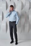 Bedrijfsmens die op telefoon againsts muur spreken in modern bureau Stock Afbeelding
