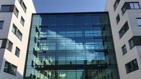 Bedrijfsmens die in silhouet door een glasgang lopen in de moderne bureaubouw met bezinningen van blauwe hemel en witte wolken stock videobeelden