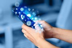 Bedrijfsmens die slimme telefoon met media pictogrammen houden Royalty-vrije Stock Foto