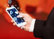 Bedrijfsmens die slimme telefoon met media pictogrammen houden Royalty-vrije Stock Afbeeldingen