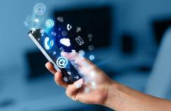Bedrijfsmens die slimme telefoon met media pictogrammen houden Royalty-vrije Stock Foto's