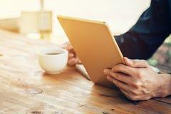 Bedrijfsmens die tablet op houten lijst in koffiewinkel gebruiken Stock Fotografie