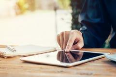 Bedrijfsmens die tablet op houten lijst in koffiewinkel gebruiken Stock Foto's