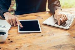 Bedrijfsmens die tablet op houten lijst in koffiewinkel gebruiken Royalty-vrije Stock Foto's