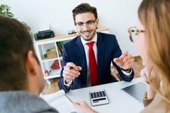 Bedrijfsmens die termijnen van contract verklaren aan zijn cliënten in het bureau stock afbeelding