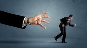 Bedrijfsmens die vanaf een reusachtig handconcept lopen Stock Afbeeldingen