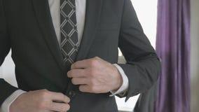Bedrijfsmens die in wit overhemd zijn kostuumjasje dichtknopen stock footage