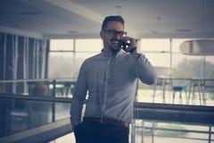 Bedrijfsmens die zich in de bedrijfsbouw bevinden Het bedrijfsmens spreken Royalty-vrije Stock Foto's