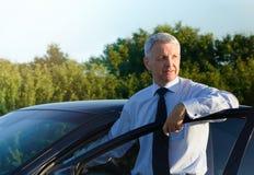 Bedrijfsmens die zich dichtbij de auto bevinden Stock Foto