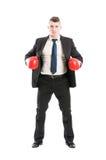 Bedrijfsmens die zich met rode bokshandschoenen bevinden Stock Foto