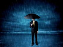 Bedrijfsmens die zich in regen met een paraplu bevinden Stock Foto's
