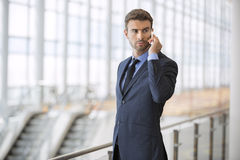 Bedrijfsmens die zich sprekend op zijn ernstige celtelefoon bevinden Royalty-vrije Stock Foto's