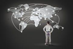 Bedrijfsmens die zich voor wereldkaart bevinden Royalty-vrije Stock Fotografie