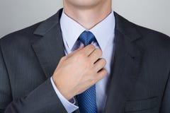 Bedrijfsmens die zijn halsband aanpassen stock afbeeldingen