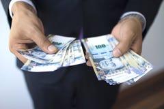Bedrijfsmens in een kostuum die 100 zolenrekeningen, Peruviaans muntconcept tellen stock afbeelding