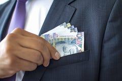 Bedrijfsmens in een kostuum die 100 zolenrekeningen, Peruviaans muntconcept verbergen royalty-vrije stock foto's