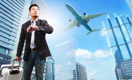 Bedrijfsmens en het behorende bagage letten op aan hemel en hand watc Stock Fotografie
